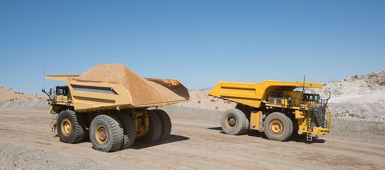 Two Komatsu mining haul trucks passing one another
