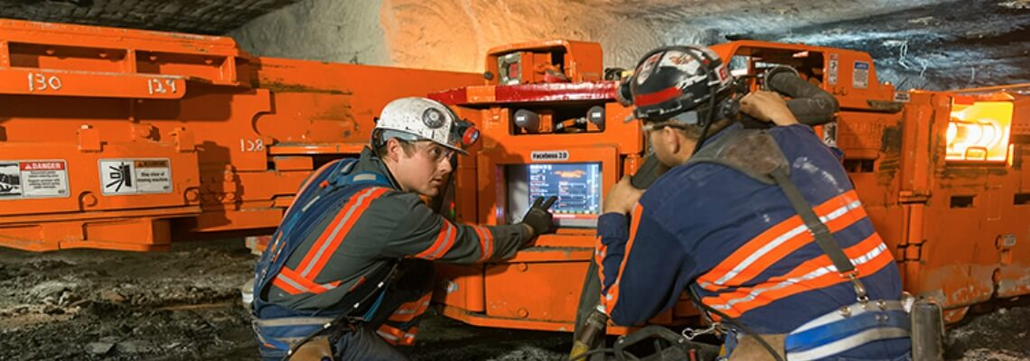 Mine personnel reviewing technology on Joy underground mining equipment
